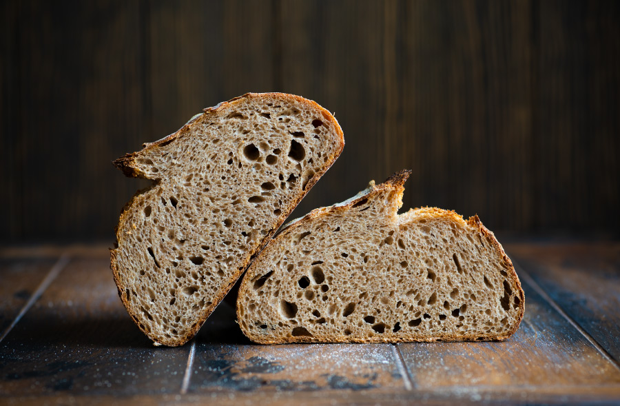 Halved sourdough bread on a wooden table showing the crumb