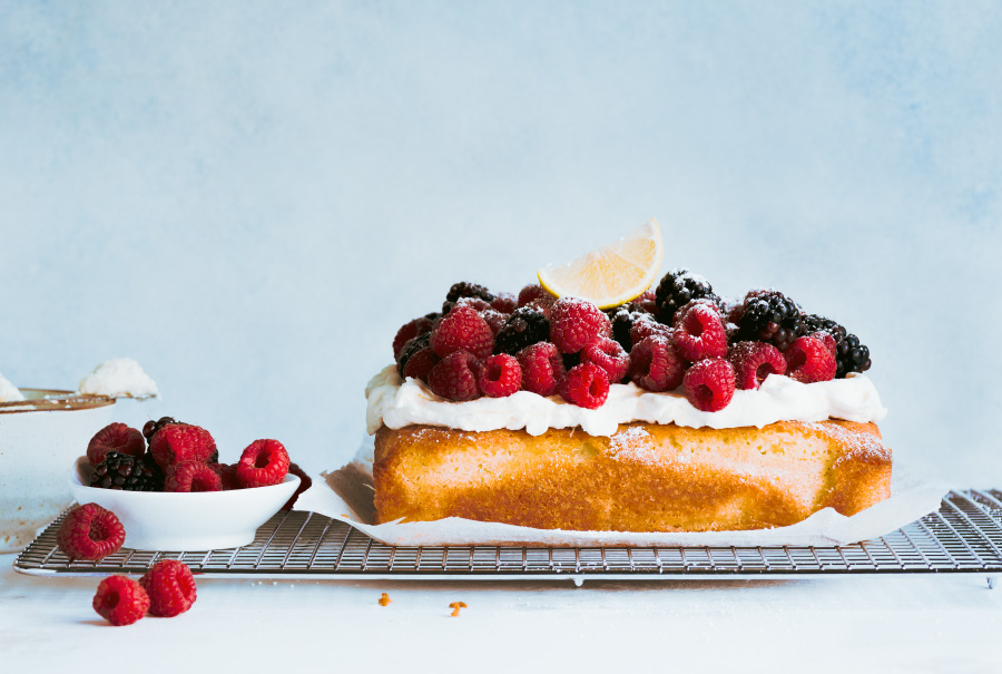 The whole lemon cake with cream and berries on cooling rack