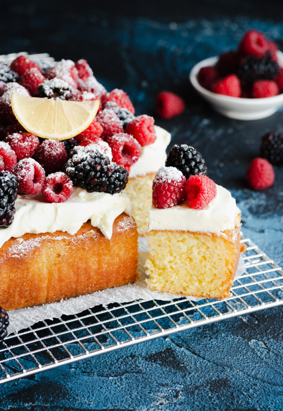 Lemon cake on a cooling rack with one piece out