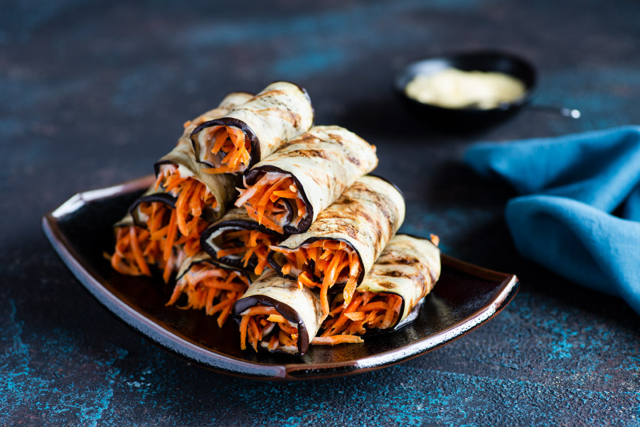 eggplant rolls with korean-style carrot dalad on a plate